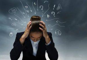 Γυναίκα που πιάνει το σκυμμένο κεφάλι της με τα χέρια της δείχνοντας να βρίσκεται σε κατάσταση άγχους που θα μπορούσε να εξελιχθεί σε κρίση πανικού