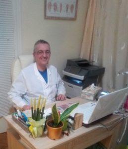 ο Ιατρός Φυσίατρος Θεόδωρος Γκατζούνης κάθετε στην λευκή καρέκλα του γραφείου στο ιατρείο του παρουσιάζοντας το άρθρο για την για την ολιστική θεραπεία σε διάστρεμμα αστραγάλου